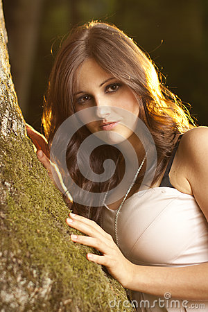 Brunet girl in a magic forest on moss