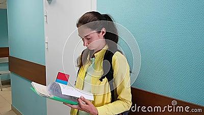 Brunetki dziewczyny stojaki przeciw ścianie w instytucji czekać na jej trzepnięcia i zwrot przez papieru zdjęcie wideo