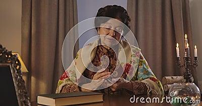 Brunette anciana caucásica con mango juntando cartas y barajándolas La adivina femenina seria parece metrajes