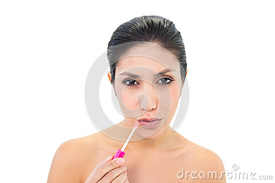 Brunette applying lip gloss and pouting at camera