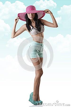 Brunette atractivo con cortocircuitos y el sombrero