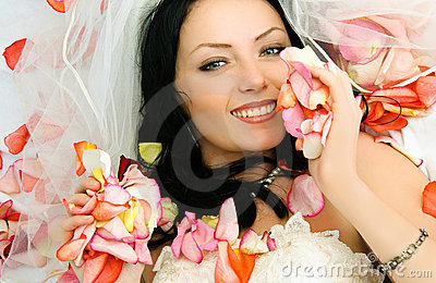 Brunette bride on the bed covered with rose leaves