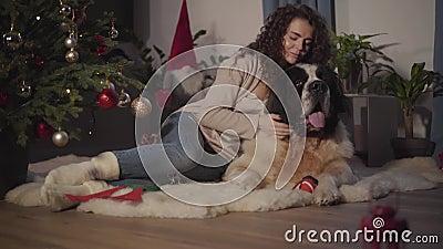 Brunette Caucasienne en tenue décontractée en train d'attraper un gros chien et de mettre la tête sur le dos de son animal de com banque de vidéos