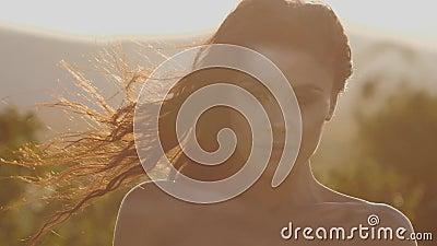 Brunette con el pelo largo de aspecto oriental en los rayos del atardecer Movimiento lento almacen de video