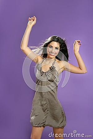 Brunette dancing at studio on purple background