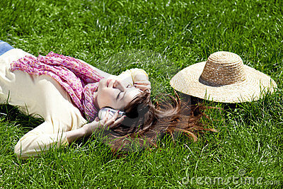 Brunette girl with headphone lies in the park.