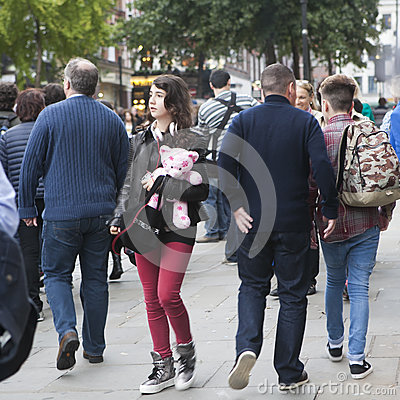 Free Brunette Girl In Headphones, In Red Jeans, A Leather Jacket Holds A Pink Teddy Bear Wading Through The Crowd Stock Images - 88596864