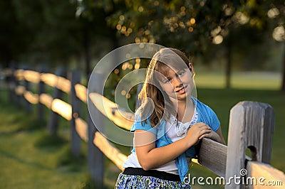 Brunette girl leaning against wooden fence