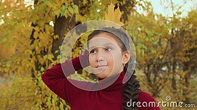 Brunette girl met braids met maple leaf achter hoofd als koningin in in het herfstpark Portret girl tiener met geel stock footage