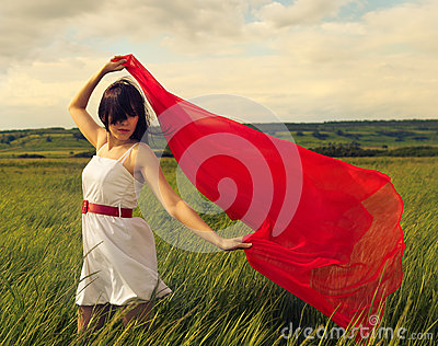 Brunette girl with red fabric in summer day