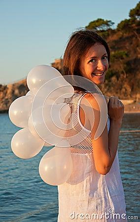 Brunette girl with white balloons on sunny beach