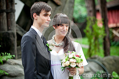 Brunette groom and bride standing close to each other