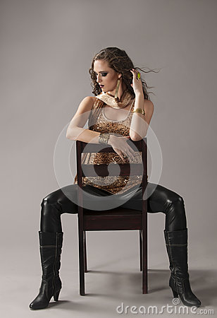 Free Brunette In Black And Gold Grunge Outfit, Seated On Black Chair Royalty Free Stock Photography - 68686277
