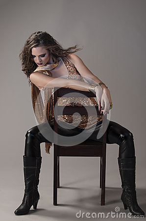 Free Brunette In Black And Gold Grunge Outfit, Seated On Black Chair Royalty Free Stock Image - 68686286