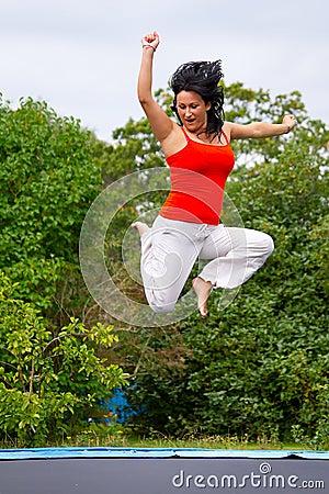 Brunette jumping on trampoline