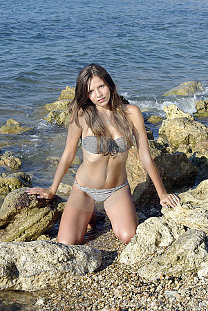 Brunette kneeling on shore