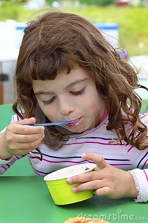 Brunette little girl eating ice cream