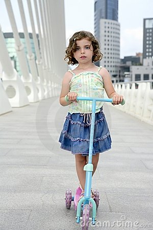 Brunette little girl with scooter in the city