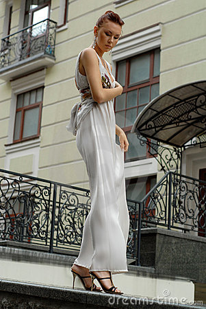Brunette in long dress near a hotel