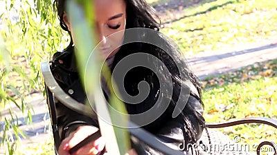 Brunette Mädchen in dunkler Lederjacke auf einer Bank im Park zwischen den wilden Zweigen stock video footage