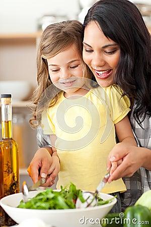 Brunette mother helping her daughter prepare salad