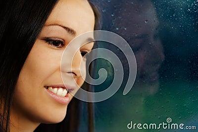 Brunette portrait, standing by rainy window.