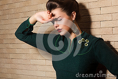 Brunette Sad Woman in Green Dress over Brick Wall