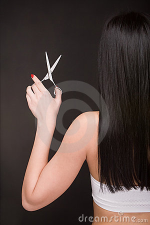 Brunette with scissors of the hairdresser
