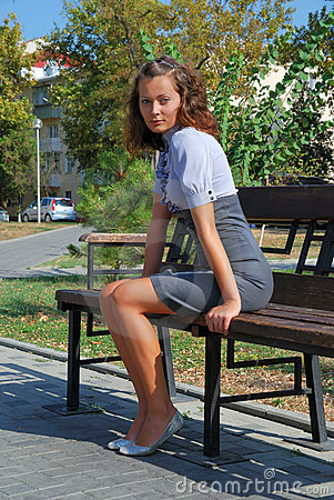 Brunette sits on bench.