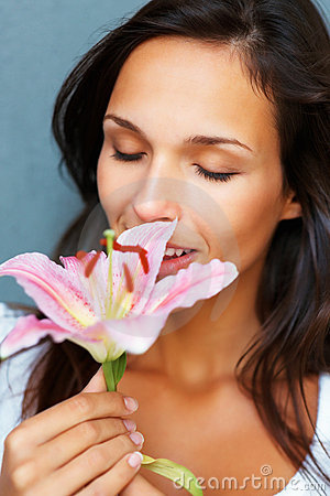 Brunette smelling stargazer lily with eyes closed