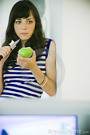 Brunette standing/eating apple