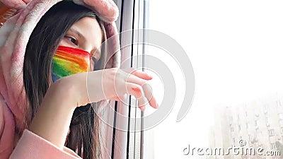 Brunette Teenagermädchen in einer medizinischen Maske, die in hellen Regenbogenfarben gestrichen ist, steht mit der Hand auf Glas stock video footage