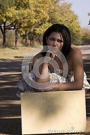 Morena triste com mala de viagem