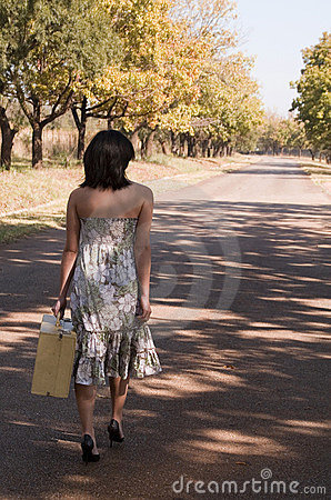 Brunette walking with suitcase