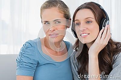Brunette wearing headphones with her friend listening