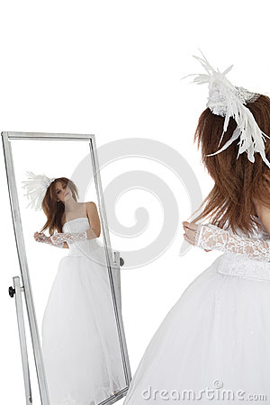 Brunette in wedding gown looking at mirror over white background