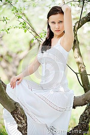 Brunette in white dress sitting