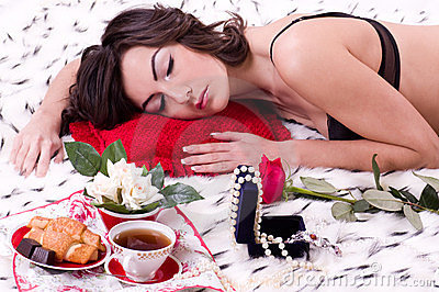 brunette woman in bed with gifts