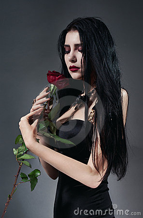 Brunette woman in black dress with red rose