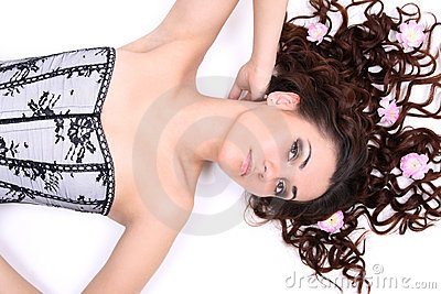 Brunette woman in corset lying with flowers