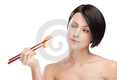 Brunette woman holding sushi with a chopsticks