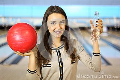 Brunette woman holds ball and bottle in bowling
