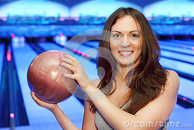 Brunette woman holds ball and smiles in bowling