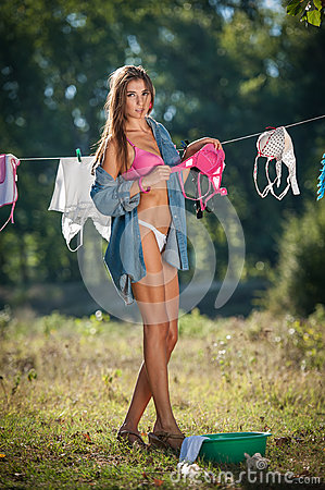 Free Brunette Woman In Bikini And Shirt Putting Clothes To Dry In Sun. Sensual Young Female With Long Legs Putting Out The Washing Stock Photography - 57979402