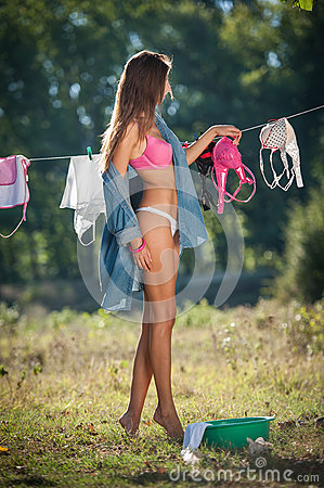 Free Brunette Woman In Bikini And Shirt Putting Clothes To Dry In Sun. Sensual Young Female With Long Legs Putting Out The Washing Stock Photo - 57979430