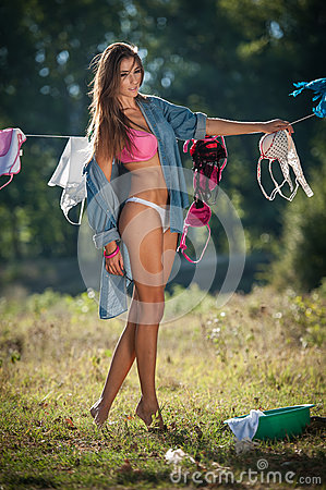 Free Brunette Woman In Bikini And Shirt Putting Clothes To Dry In Sun. Sensual Young Female With Long Legs Putting Out The Washing Stock Image - 57979441