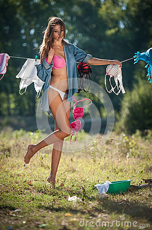 Free Brunette Woman In Bikini And Shirt Putting Clothes To Dry In Sun. Sensual Young Female With Long Legs Putting Out The Washing Stock Images - 57979474