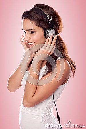 Brunette woman listening tbrunette woman listening to the music wearing headphones