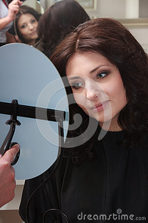 Brunette woman with new hairstyle looking at mirror. In hair salon.