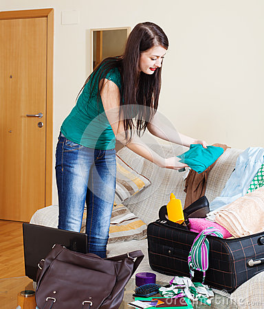 Brunette woman packing suitcase